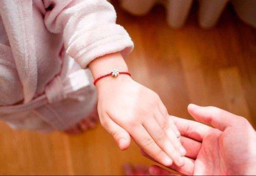 Красная нить на руке ребенка